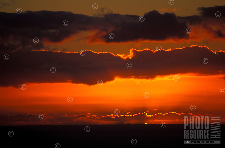The sun sinks below the horizon of the Pacific Ocean with dramatic overhead clouds, as seen from Maui.