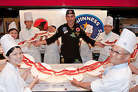 Nico Jimenez from Spain poses with students from Hattori cooking school after he breaks the world record for the longest slice of meat with an Iberico Ham from sposor, Iberselec, that he sliced to a length of 13 metres, 35 centimetres. This broke his own world record, set in 2008, by three centimetres. Hattori school of nutrition, Yoyogi, Tokyo, Japan. September 23rd 2010