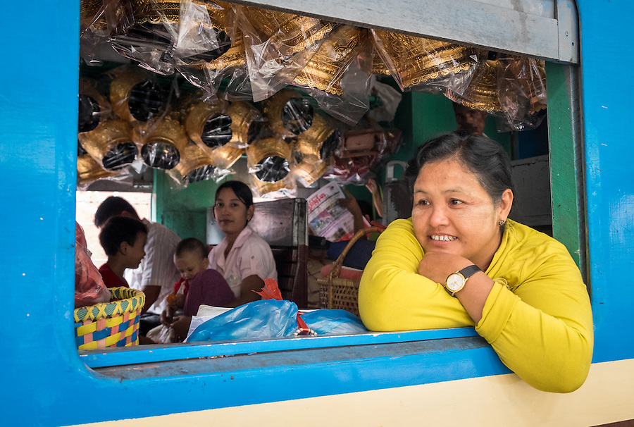 YANGON, MYANMAR - CIRCA DECEMBER 2013: Smiling burmese woman looking away from a train window while awaits train to depart from Yangon Central Railway Station