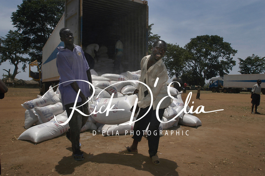 Workers unload one of five World Food Program semi-trucks of food for residents of Awer camp for internally displaced persons 15 kilopmeters northwest of Gulu, March 25, 2004. More than 2 million people are displaced across northern Uganda, resulting from the conflict with the Lord's Resistance Army. The LRA kidnaps people from their rural homes and schools to press them into service as porters and soldiers. The conflict is entering its 18th year. (Rick D'Elia)