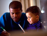 African-American father and son working together at desk, family activities, parents, children, Black child, man. Greg and James Churchman.