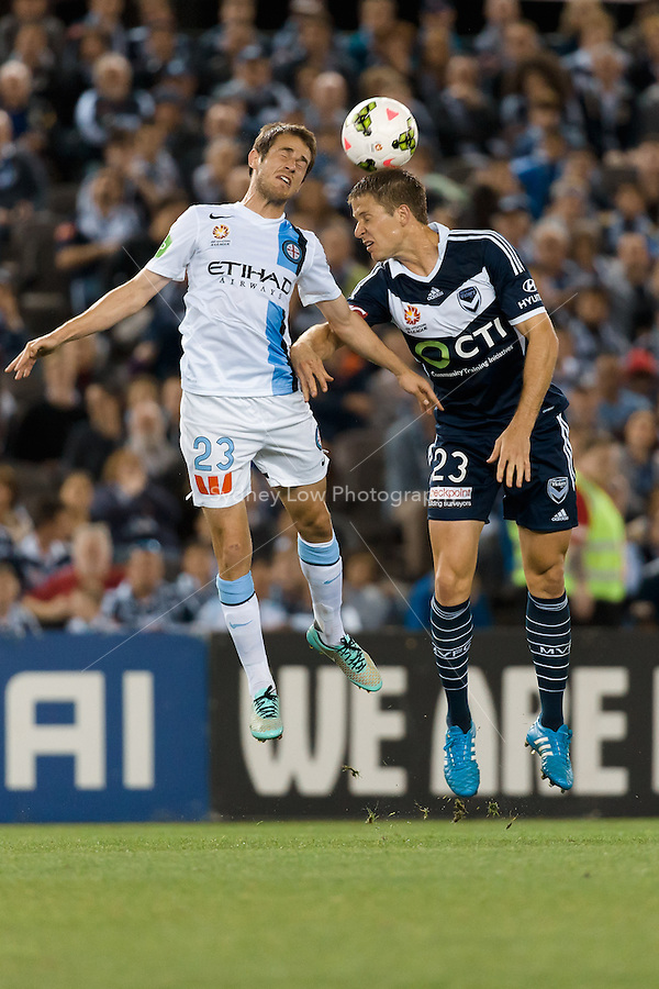 Mate DUGANDZIC of Melbourne City and Adrian LEIJER of the Victory jump for the ball in the round 3 match between Melbourne  Victory and Melbourne City in the Australian Hyundai A-League 2014-15 season at Etihad Stadium, Melbourne, Australia.