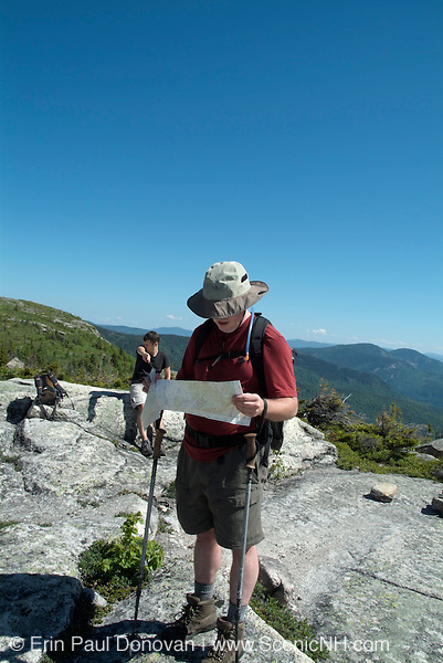 Hiker reading map on Baldface Cirlce Trail during the spring months in the White Mountains, New Hampshire USA