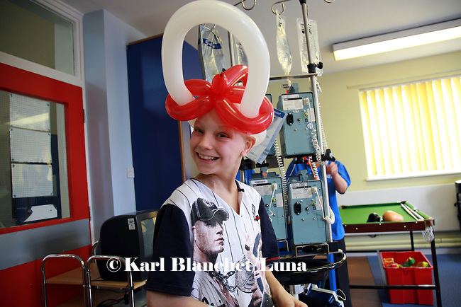 Jamie receives a nice original hat from the clowns as a recognition of his skills as a magician. Oncology ward at the Royal Manchester Children hospital.