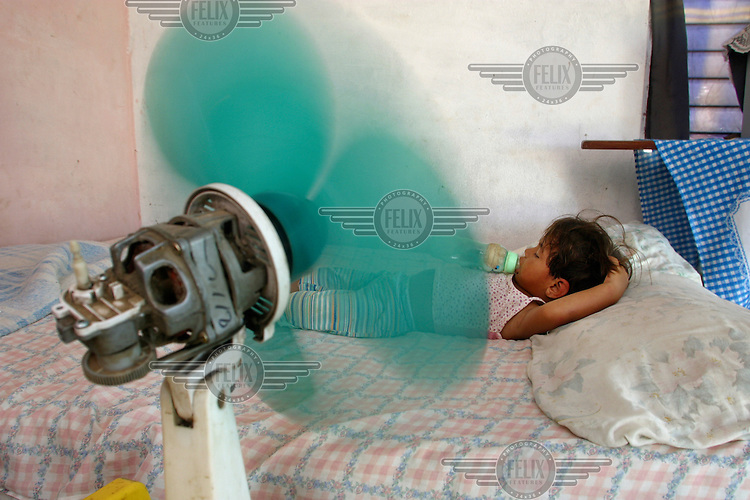 A baby sleeps by an electrical fan. The child of Colombian refugees, she is the only person in the family with any legal rights in Venezuela.