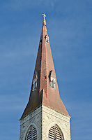 The St Mary Carmelite Church Steeple rises above the streets of Joliet, Illinois against a blue sky