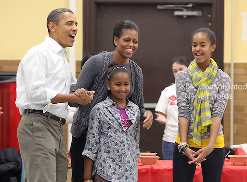 """United States President Barack Obama and daughters Malia and Sasha sign """"Happy Birthday"""" to First Lady Michelle Obama on her birthday on Monday, January 17, 2011 as the first family participates in a community service event at the Stuart Hobson Middle School Service Project in Washington, D.C.  to honor the birthday of Dr. Martin Luther King Jr.  .Credit: Dennis Brack / Pool via CNP"""