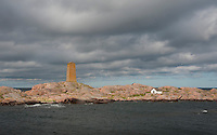 A fast moving sunbeam spotlights Segelskär day beacon as threatening storm clouds sweep past this outer skerry in the Gulf of Finland between Helsinki and Hanko.