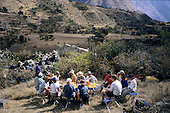 Inca Trail, Peru. Group of tourists eating lunch at a folding table whilst guides and porters eat sitting on rocks behind.