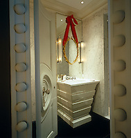 A glimpse through the open door of a bathroom with a bespoke corner basin