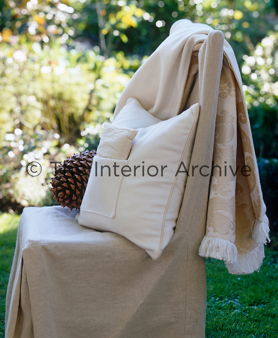 A garden chair is transformed with a loose cover of natural linen, sufficiently elegant to grace an outdoor dinner party