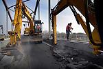 AMSTERDAM - In Amsterdam gaan medewerkers van GMB Beton- en industriebouw enthousiast aan de gang met het slopen van het betonnen wegdek op de Amsterdamsebrug over het Amsterdam-Rijnkanaal. Nadat men lang heeft moeten wachten voordat het beton op het nieuwe gedeelte uitgehard is, en de rijbanen eindelijk verplaatst zijn, nemen ze - nog voordat de bus er als eerste overheen mag - direct de vloer onder handen. Het wegek van de uit de jaren vijftig daterende staalboogbrug is de afgelopen jaren flink versleten door toenemende verkeersdrukte en de steedse zwaardere vrachtwagens. De werkzaamheden zijn begonnen in september en hadden in vier maanden klaar moeten zijn.  COPYRIGHT TON BORSBOOM