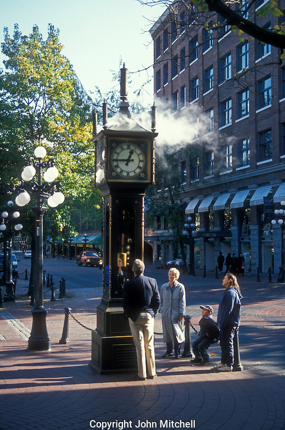 Tourists looking at the historic steam clock on Water Street in Gastown, Vancouver, British Colombia, Canada
