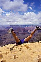 Man nose diving into Grand Canyon, with the legs in the air. Arizona, USA