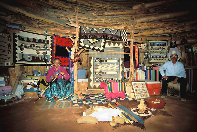 Two Navajo elders sit inside a traditional Navajo log hogan decorated with a traditional weaving loom and several rugs that are for sale to tourist who visit Monument Valley, Arizona