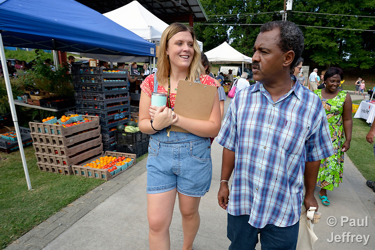 Monique Lohmeyer, a case manager for Church World Service, walks with Yosef Birhane, a refugee from Eritrea, through the Durham Farmers' Market in Durham, North Carolina. The market's Double Bucks program allows consumers with EBT cards to double their purchasing power.<br /> <br /> Church World Service resettles refugees in North Carolina and throughout the United States.<br /> <br /> Photo by Paul Jeffrey for Church World Service.