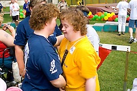 Award winning women athletes embrace each other. Special Olympics U of M Bierman Athletic Complex. Minneapolis Minnesota USA