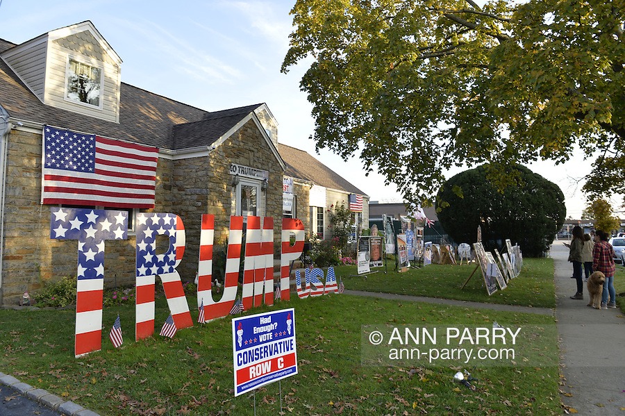 "Bellmore, New York, USA. November 2, 2016. Neighbors and others stand talking with Eileen Fuscaldo in front of her home, with large letters spelling out TRUMP, a ""Vote Conservative Row C"" political banner, and other displays in support of the Republican presidential candidate, Donald Trump, and against Democrat Hillary Clinton."