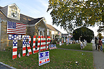"""Bellmore, New York, USA. November 2, 2016. Neighbors and others stand talking with Eileen Fuscaldo in front of her home, with large letters spelling out TRUMP, a """"Vote Conservative Row C"""" political banner, and other displays in support of the Republican presidential candidate, Donald Trump, and against Democrat Hillary Clinton."""