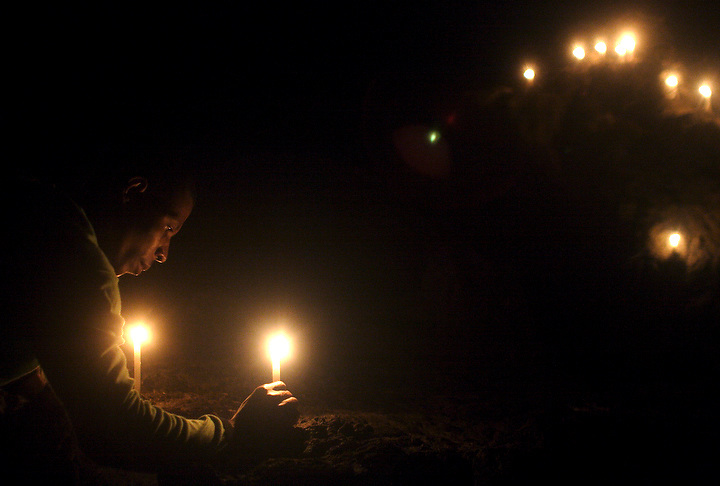 NUQUÍ, EL CHOCO, COLOMBIA -- DECEMBER 8:  A young man lights candles, each representing a wish for the New Year, near Nuqui on December 8, 2005. Nuquí is a small town on Colombia's isolated and untamed Pacific coast, an area sandwiched between endless miles of trackless rainforest and the Pacific Ocean. (Photo by Dennis Drenner/Aurora).