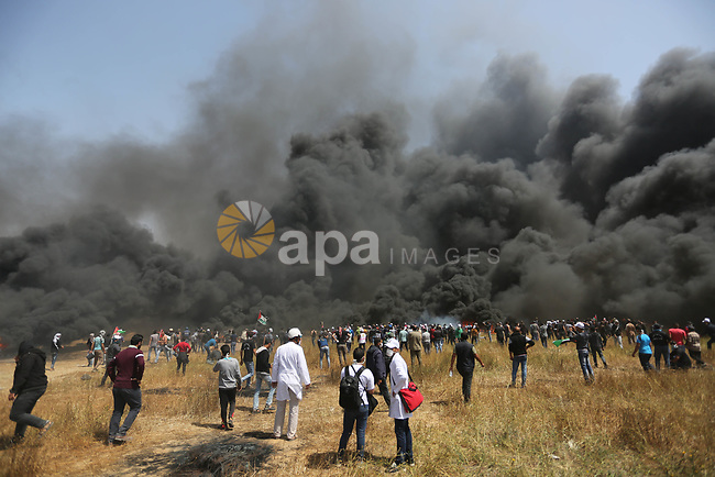Palestinian protesters burn tires to protect themselves from shots of Israeli soldiers during clashes in a tent city protest at the Israel-Gaza border, demanding the right to return to their homeland, in Khan Younis in the southern Gaza strip on April 6, 2018. Photo by Ashraf Amra