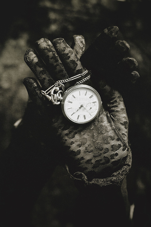 Two hands in black lace gloves holding necklace with open golden pocket watch in sepia tone