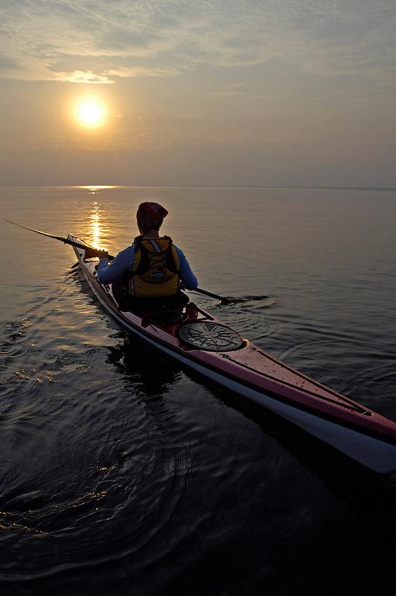 A female sea kayaker paddles a red kayak on Lake Superior near Grand Marais Michigan.