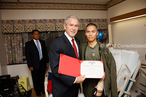 Bethesda, MD - July 3, 2008 -- United States President George W. Bush awards a Purple Heart medal and citation to United States Navy Hospitalman Apprentice Jefferson Talicuran of Chula Vista, California,Thursday, July 3, 2008, at the National Naval Medical Center in Bethesda, Maryland..Credit: Eric Draper - White House via CNP