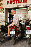 VIETNAM, Saigon, restaurant Pho Hoa aka Pho Hoa Pasteur, the owner sits on a moped out front of his establishment, Ho Chi Minh City