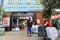 CHINA Guangzhou , african trader buy  textiles in export- and wholesale markets which the ship to Africa for their shops, Nigerian Ikechukwu Nwanzi in front of his Hotel with chinese porter / CHINA , Provinz Guangdong , Metropole Guangzhou (Kanton) , Haendler aus Afrika kaufen in Grosshandels-/Exportmaerkten Textilien fuer Ihre Laeden in Afrika ein, Nigerianer Ikechukwu Nwanzi vor seinem Hotel mit den gekauften Waren und chinesischem Porter