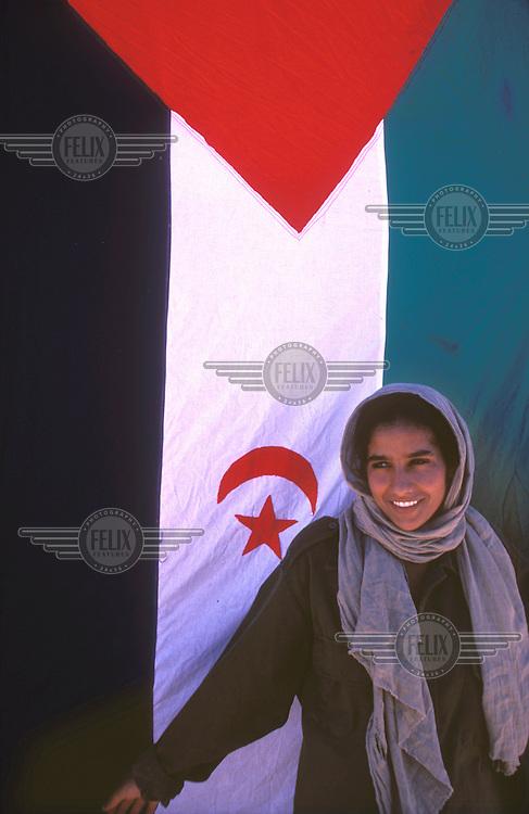 © JC Tordai / Panos Pictures..Western Sahara, ALGERIA..A Sahrawi girl with the Polisario flag. S.A.D.R.