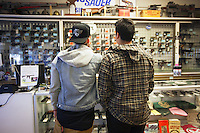 USA. Arizona state. Avondale town. Two young customers, both major men, are interested in buying a firearm at the gun shop AZFirearms.com with over 1'000 guns in stock. A firearm is a portable gun, being a barreled weapon that launches one or more projectiles often driven by the action of an explosive force. Most modern firearms have rifled barrels to impart spin to the projectile for improved flight stability. The word firearms usually is used in a sense restricted to small arms (weapons that can be carried by a single person). The right to keep and bear arms is a fundamental right protected in the United States by the Second Amendment of the Bill of Rights in the Constitution of the United States of America and in the state constitutions of Arizona and 43 other states. 25.01.16 © 2016 Didier Ruef