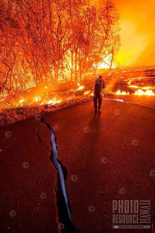 June 2018: A man takes photos of the Kilauea Volcano eruption while standing near a pavement crack that emits blue methane gas, Leilani Estates, Puna, Big Island of Hawai'i.