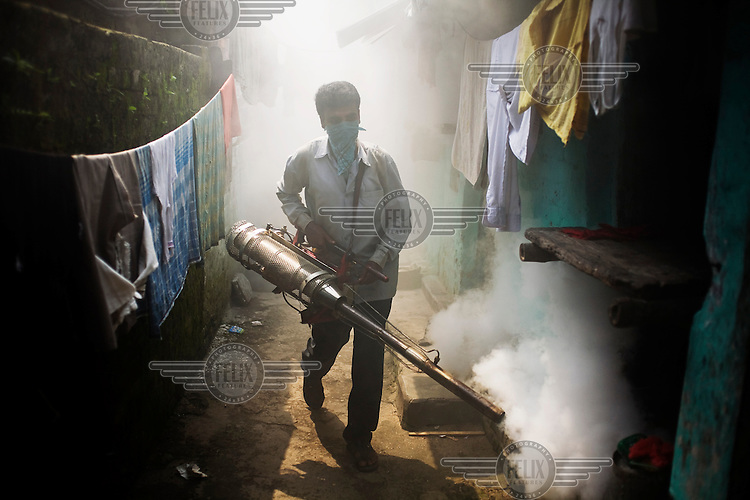 In Calcutta, a man sprays fog to kill mosquitoes in order to protect people from malaria.