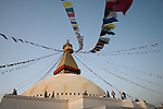People walk around Boudhanath or Bodnath Stupa, the largest stupa in Nepal, as the sun sets in Kathmandu.