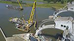 Foto: VidiPhoto<br /> <br /> AMERONGEN &ndash; In de stuw bij Amerongen is woensdag met twee grote hijsbokken het eerste deel verwijderd van de oude vizierschuif. Vorig jaar werd de stuwboog aan de noordzijde vervangen. Nu is de tweede boog aan de beurt. Het vormt een onderdeel van een uniek stukje bouwgeschiedenis in ons land. De waterkeringen van Amerongen, Hagestein en Driel in de Rijn, hebben de enige stuwbogen ter wereld. Bovendien worden ze vrijwel gelijktijdig vervangen. In 2020 moet het enigszins vertraagde project (met een aanneemsom van 100 miljoen euro) gereed zijn. Amerongen wordt het eerst helemaal afgewerkt, mede doordat bij voorbereidende werkzaamheden aan de stuw in Driel -september vorig jaar- een duiker om het leven kwam. In Amerongen wordt de boog in zes stukken gezaagd en in delen verwijderd. Daarna volgt het inhijsen van de nieuwe vizierschuif in drie delen. Over zes weken moet de stuw in Amerongen helemaal gereed zijn. Daarna wordt begonnen met de werkzaamheden in Driel. Opdrachtgever is Rijkswaterstaat, hoofdaannemer is Siemens.