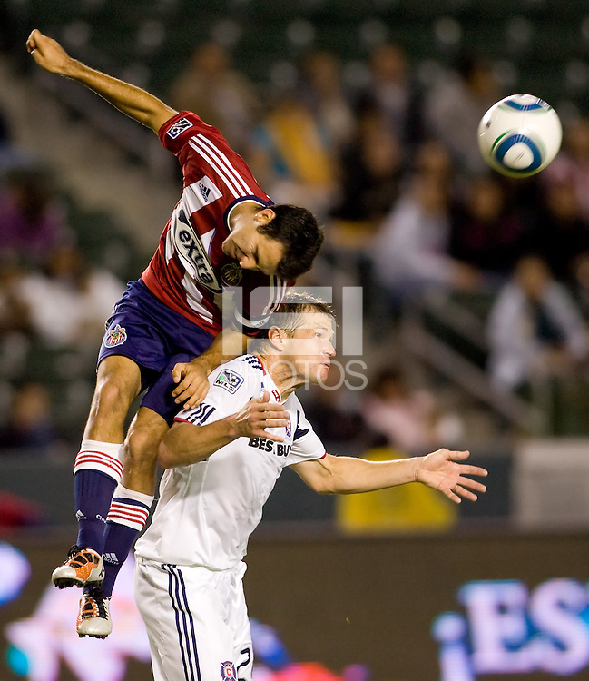 Chivas USA midfielder Jonathan Bornstein (r) goes over the top of Chicago Fire veteran Brian McBride (w) in both of there last matches in the MLS. The Chicago Fire defeated CD Chivas USA 3-1 at Home Depot Center stadium in Carson, California on Saturday October 23, 2010.