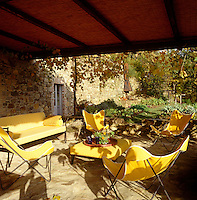 The bright yellow covers of garden chairs on the covered terrace echo the autumn tints in the garden beyond