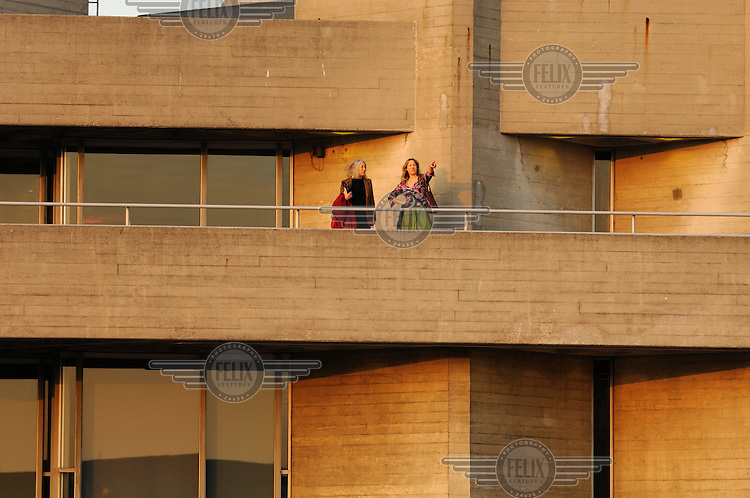 People on an upper terrace of London's National Theatre before a performance.