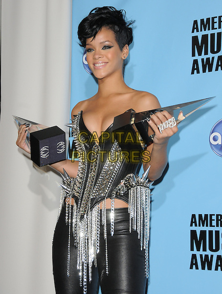 RIHANNA .The 2008 American Music Awards held at Nokia Theatre Live L.A. in Los Angeles, California, USA..November 23rd, 2008      .AMA AMAs pressroom half length award trophy trophies black strapless top leather spikes studs studded chains silver ring .CAP/DVS.©Debbie VanStory/Capital Pictures.