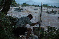 In order to reach a good spot to fish with his bamboo net, a fisherman descends the steep and slippery banks of the Mekong river in front of the Liphi Waterfalls. A false step and he could fall into the dangerous current and die. 04/08/2013 © Thomas Cristofoletti / Ruom