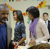 First Lady Michelle Obama, with the help of her daughter Malia Obama, standing next to her, pack and give bags of food to area residents at Martha's Table on Wednesday, November 24, 2010, in Washington, DC.  .Credit: Leslie E. Kossoff - Pool via CNP