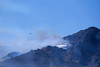 870000358 a los angeles county fire fighting helicopter flies over a burning hillside and another chopper does an aerial retardant drop in the path of the topanga fire in the hills above the san fernando valley in southern california