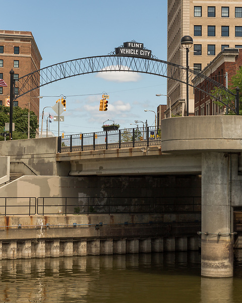 August 7, 2016. Flint, Michigan.<br />  A sign along the Flint River in downtown reminds visitors of the city's car manufacturing past. <br />  In April 2014, the city of Flint switched its water source from the Detroit Water and Sewerage Department to using the Flint River in an effort to save money. When the switch occurred, the city failed to have corrosion control treatment in place for the new water. This brought about a leaching of lead from pipes into the water, increasing the lead content in the drinking water to levels far above legal limits. After independent sources brought this to light, the city admitted the water was unsafe and legal battles have ensued between resident and the local and state governments.