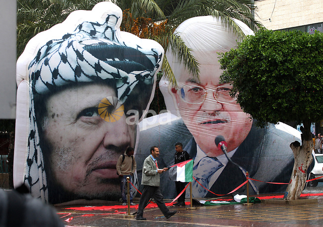 Palestinians walk pass a mural of the late Yasser Arafat and current Palestinian President Mahmoud Abbas during the eighth anniversary of the death of the late leader Yasser Arafat, in the West Bank city of Nablus on November 11, 2012. Palestinians are coordinating with Russia, as well as Swiss and French experts, on the exhumation of Arafat who died in a French military hospital near Paris on November 11, 2004, and who French experts were unable to say what had killed him. Many Palestinians are convinced he was poisoned. Photo by Nedal Eshtayah