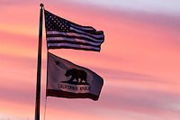 The U.S. and California State flags against a sunset sky.