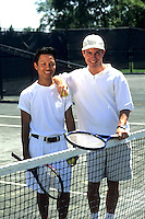 Affluent gay male couple enjoy playing tennis and spending time together on a warm summer's day