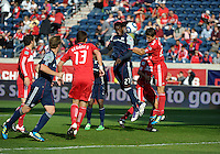 New England midfielder Shalrie Joseph (21) sends a header on goal while being defended by Chicago defender Josip Mikulic (23, right).  The Chicago Fire defeated the New England Revolution 3-2 at Toyota Park in Bridgeview, IL on Sept. 25, 2011.