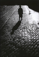 Silhouetted man on cobblestones
