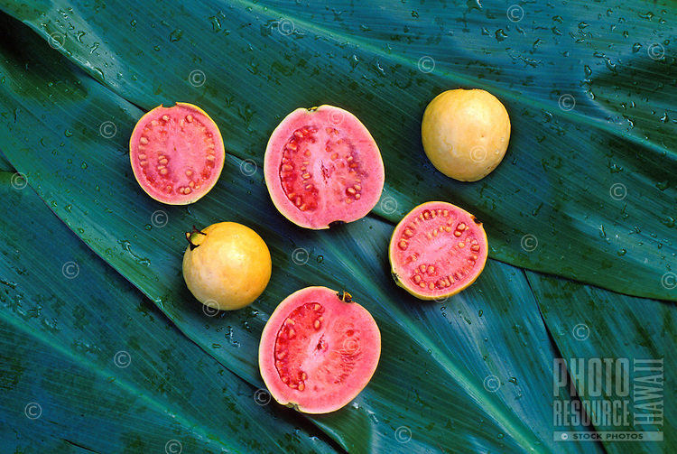 Guava fruits cut open on green ti leaves